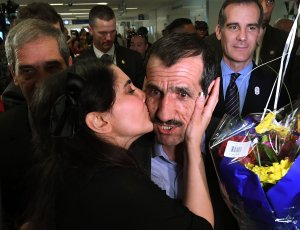 Ali Vayeghan, right, is kissed by his niece Marjan Vayghan upon arrival at Los Angeles International Airport after he was previously barred entry and deported from the U.S. under President Donald Trump's travel ban on Feb. 2, 2017. (Credit: Mark Ralston / AFP / Getty Images)