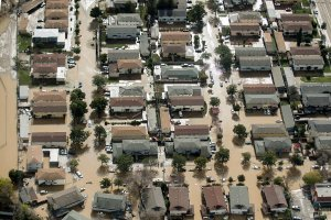 Floodwaters surround homes and cars on Feb. 22, 2017, in San Jose. (Credit: Noah Berger / AFP / Getty Images)