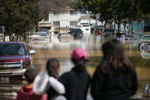 People look at cars and homes engulfed in floodwaters on Feb. 22, 2017, in San Jose. (Credit: Elijah Nouvelage / Getty Images)
