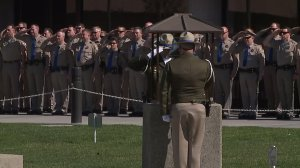Fellow CHP officers salute at a bell toll ceremony for Lucas Chellew at the CHP Academy on Feb. 23, 2017. (Credit: KTXL)