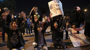 Demonstrators kneel in front of an Anaheim police formation to protest a confrontation between an off-duty LAPD officer and a group of teenagers. (Credit: Marcus Yam / L.A. Times)
