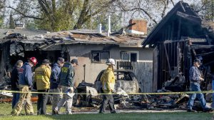 NTSB and Riverside fire investigators on Feb. 28, 2017, examine the scene of a small plane crash that killed three people and destroyed two homes the previous evening in Riverside. (Credit: Irfan Khan / Los Angeles Times)