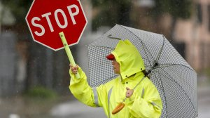 Crossing guard Maria Brito escorts pedestrians at Ford Boulevard and Verona Street in East Los Angeles during morning showers on Feb. 6, 2017. (Credit: Mark Boster / Los Angeles Times)