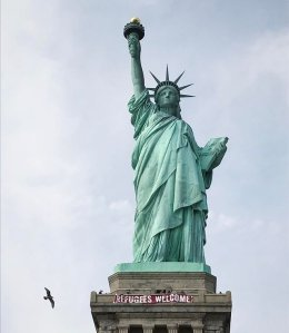 "A 20-foot red and white banner that read ""Refugees welcome"" hung across the Statue of Liberty on Tuesday, Feb. 21, 2017. (Credit: Vitória Londero)"