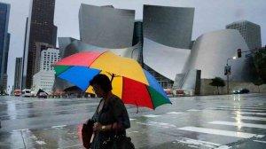 A woman holding an umbrella walks through Downtown L.A. amid a rainstorm in December 2016. (Credit: Irfan Khan / Los Angeles Times)