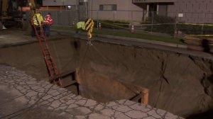 Crews on Feb. 20, 2017 continued to repair a sinkhole in Studio City where a woman fell in while driving her car days earlier. (Credit: KTLA)