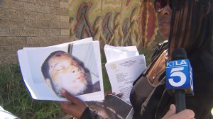 Nefertiti Brown holds up a picture of her son, who she says was beat to death while in police custody. (Credit: KTLA)