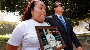 Teresa Dominguez holds a photo of her son, 14-year-old Jesse Romero, next to attorney Humberto Guizar as they hold a news conference to discuss a federal lawsuit filed against the city in the shooting death on June 23, 2017. (Credit: Al Seib / Los Angeles Times)