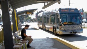 A Metro rider waits for an Orange Line bus at the North Hollywood station. That busway will be the first route to run only electric buses. (Irfan Khan / Los Angeles Times)