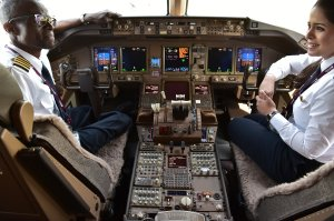 Qatar Airways pilots chat in the cockpit of a Boeing 777 jet airliner on display at the International Paris Air Show in Le Bourget outside Paris on June 22, 2017. (Credit: Christophe Archambault / AFP / Getty Images)