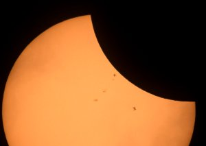 The International Space Station (bottom right), with a crew of six onboard, is seen in silhouette as it transits the sun at roughly five miles per second during a partial solar eclipse, Aug. 21, 2017, near Banner, Wyoming. (Credit: Joel Kowsky/NASA via Getty Images)