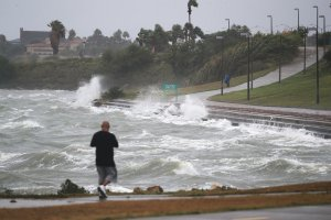 A man walks near the bay waters as they churn from approaching Hurricane Harvey on August 25, 2017 in Corpus Christi, Texas. (Credit: Joe Raedle/Getty Images)
