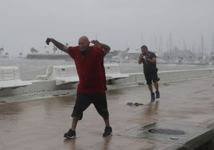 Raul Barral and Carlos Guerra (from left) walk through high wind and driving rain together before the arrival of Hurricane Harvey on Aug. 25, 2017, in Corpus Christi, Texas. (Credit: Joe Raedle / Getty Images)