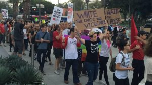 Dozens of demonstrators gathered in front of LAPD headquarters Saturday evening to protest the violence in Charlottesville. (Credit: Carlos Lozano/ Los Angeles Times.)