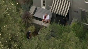 The man shot during a robbery in Mid-Wilshire can be seen sitting on a porch, bleeding. (Credit: KTLA)