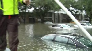 Amid multiple submerged vehicles, a boater navigates the floodwaters near Houston as he helps with rescue efforts on Aug. 29, 2017. (Credit: KTLA)