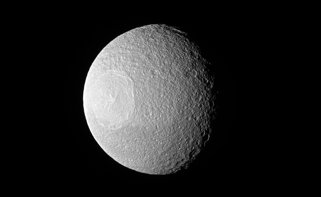 "Tethys, one of Saturn's larger icy moons, vaguely resembles an eyeball staring off into space in this view from NASA's Cassini spacecraft. If you ask ""Star Wars"" fans, they will tell you how strangely similar it looks to the Death Star. (Credit: NASA)"