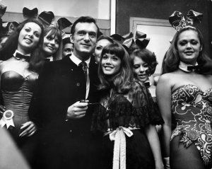 "Hugh Hefner is seen with longtime partner and Playboy model Barbi Benton, right, among ""bunny girls"" at his London Playboy Club in 1962. (Credit: Michael Webb / Getty Images)"
