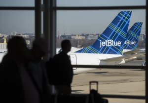Travelers walk past the tails of JetBlue airplanes in the airport terminal at Ronald Reagan Washington National Airport in Arlington, Virginia, Dec. 22, 2016. (Credit: SAUL LOEB/AFP/Getty Images)