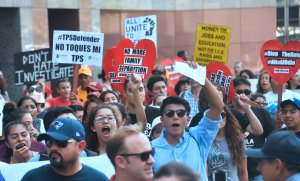 Young immigrants and supporters walk holding signs during a rally in support of Deferred Action for Childhood Arrivals (DACA) in Los Angeles on September 1, 2017.
