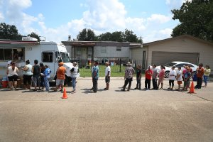 People line up to receive food and water from a Salvation Army truck after their homes were inundated with flood waters during Hurricane and Tropical Storm Harvey on Sept. 2, 2017 in Houston, Texas. (Credit: Joe Raedle/Getty Images)