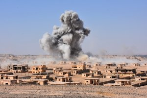 Smoke rises from buildings on the northern outskirts of Deir Ezzor on Sept. 13, 2017, as Syrian forces advance during their ongoing battle against the Islamic State group. (Credit: George Ourfalian / AFP / Getty Images)