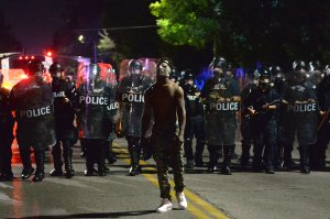 A lone protester is seen as law enforcement officers advance behind him during a protest following a not guilty verdict on Sept. 15, 2017, in St. Louis, Missouri. (Credit: Michael B. Thomas / Getty Images)