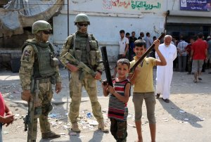 A picture taken during a press tour provided by the Russian Armed Forces on Sept. 15, 2017, shows Russian soldiers standing guard in a central street in Syria's eastern city of Deir Ezzor, as local children pose nearby. (Credit: Dominique Derda / AFP / Getty Images)