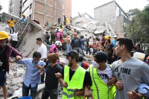 Rescuers, firefighters, policemen, soldiers and volunteers remove rubble and debris from a flattened building in search of survivors after a powerful quake in Mexico City on Sept. 19, 2017. (Credit: Ronaldo Schemidt / AFP / Getty Images)