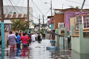 People walk in a flooded street next to damaged houses in Catano, Puerto Rico, on Sept. 21, 2017. (Credit: Hector Retamal / AFP / Getty Images)