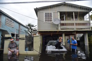 Inhabitants stand in flood water in front of a house flooded in Catano, Puerto Rico, on Sept. 21, 2017. (Credit: Hector Retamal / AFP / Getty Images)