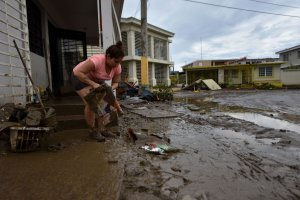A woman removes mud from her damaged house in Toa Baja, 35 km from San Juan, Puerto Rico, on Sept. 23, 2017, where Rio Plata flooded during and after the passage of Hurricane Maria. (Credit: Hector Retamal / AFP / Getty Images)
