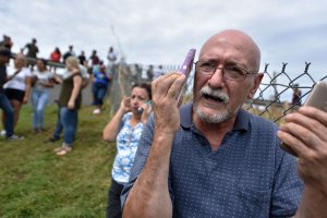 A man manages to speak by cellphone to his family in the United States from Vega Alta, 45 km north of San Juan, Puerto Rico, on Sept. 23, 2017. (Credit: Hector Retamal / AFP / Getty Images)