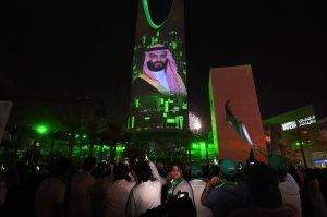 People watch a projection depicting a portrait of Crown Prince Mohammed bin Salman during an event in the capital Riyadh on late Sept. 23, 2017. (Credit: AFP/Getty Images)