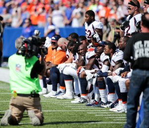 Denver Broncos players kneel during the American National Anthem before an NFL game against the Buffalo Bills on Sept. 24, 2017, at New Era Field. (Credit: Brett Carlsen / Getty Images)