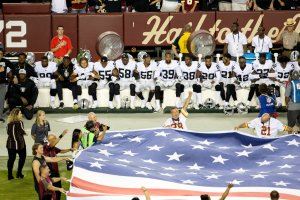 Oakland Raiders players sit during the national anthem before they take on the Washington Redskins at FedExField on Sept. 24, 2017. (Credit: Tasos Katopodis / Getty Images)