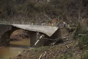 People cross a bridge what was destroyed when Hurricane Maria passed through on Sept. 27, 2017, in Corozal, Puerto Rico. (Credit: Joe Raedle / Getty Images)