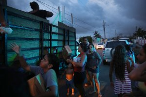 Hurricane survivors receive food and water being given out by volunteers and municipal police as they deal with the aftermath of Hurricane Maria on Sept. 28, 2017, in Toa Baja, Puerto Rico. (Credit: Joe Raedle / Getty Images)