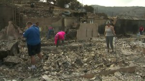 Friends of a Sunland couple who lost their home in the La Tuna Fire return to the rubble on Sept. 4, 2017. (Credit: KTLA)