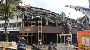 It has been days since the last person was extracted from the building alive, and the stench of death pervades the scene. Twenty bodies have been found. Crews think 10 to 20 remain. (Credit: Rong-Gong Lin II / Los Angeles Times)