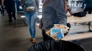 A new law will allow schools to collect unopened food items and untouched fruit for donation to food banks. In this photo from 2014, students from Washington Preparatory High are throwing away unused milk cartons, part of millions of dollars in wasted food. (Credit: Gina Ferazzi / Los Angeles Times)