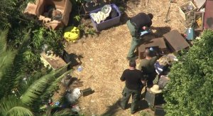 Los Angeles County Sheriff's Officials look through a Lawndale back yard where a cache of weapons was found on Sept. 29, 2017. (Credit: KTLA)