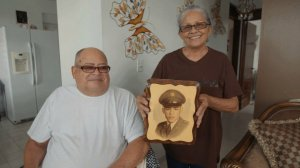Miguel Olivera and his wife Diana Aponte show a picture from his time in service. (Credit: CNN)