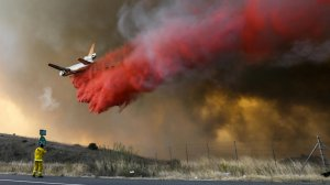 A DC-10 makes a drop as the Anahiem Hills fire rages along 241 and Santiago Canyon Rd in Orange. (Credit: Irfan Khan/Los Angeles Times)