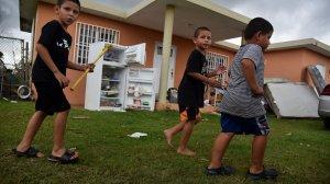 Children walk alongside hurricane-damaged furniture, in Vega Baja, Puerto Rico, on Sept. 30, 2017. (Credit: Hector Retamal/AFP/Getty Images)