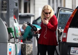 A woman prepares to pump gasoline into her vehicle at a Chevron gas station on Feb. 9, 2015, in San Rafael. (Credit: Justin Sullivan / Getty Images)