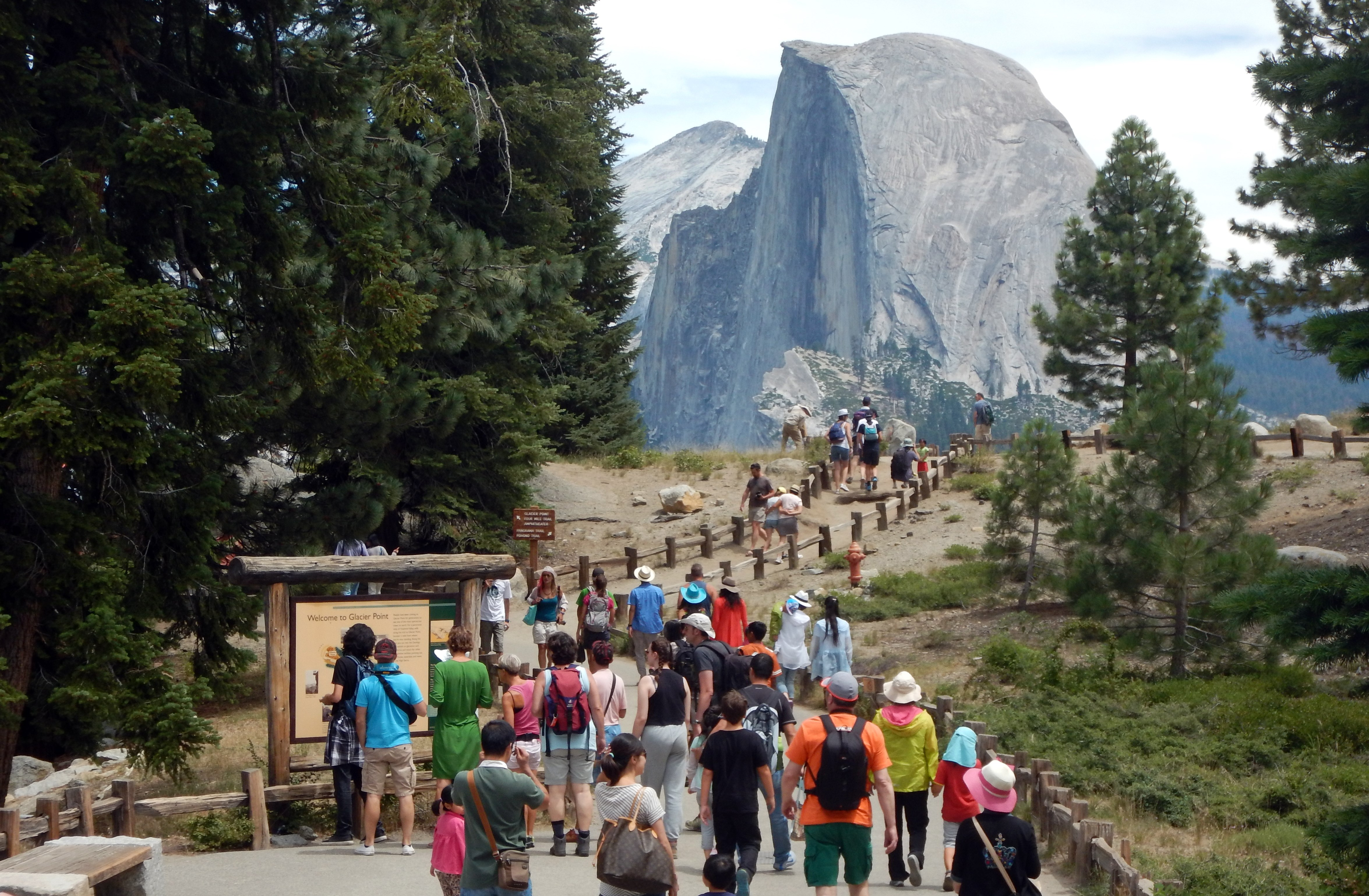 This Aug. 5, 2015, photo shows tourists walking out to Glacier Point with a background view of Half Dome at Yosemite National Park. (Credit: FREDERIC J. BROWN/AFP/Getty Images)