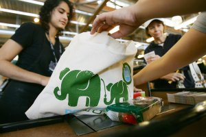 Cashier Bianca Kurian, left, hands out free reusable grocery bags at a Whole Foods in Pasadena on April 22, 2008. (Credit: David McNew / Getty Images)
