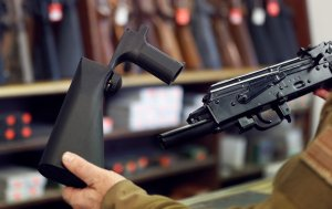 A bump stock device (left), that fits on a semi-automatic rifle to increase the firing speed, making it similar to a fully automatic rifle, is shown next to a AK-47 semi-automatic rifle (right), at a gun store in Salt Lake City on Oct. 5, 2017. (Credit: George Frey/Getty Images)