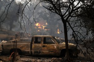 Fire consumes a home as an out of control wildfire moves through the area on Oct. 9, 2017, in Glen Ellen, California. (Credit: Justin Sullivan / Getty Images)